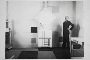 Mondrian in his Paris studio in 1933 with Lozenge Composition with Four Yellow Lines, 1933 and Composition with Double Lines and Yellow, 1933. Photo by Charles Karsten.   RKD – Netherlands Institute for Art History. © 2014 Mondrian/Holtzman Trust c/o HCR International USA