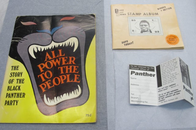 Black Panther party pamphlet and membership card. Black and Brown stamp album. Credit - Courtesy of Jon Daniel and National Museums Liverpool